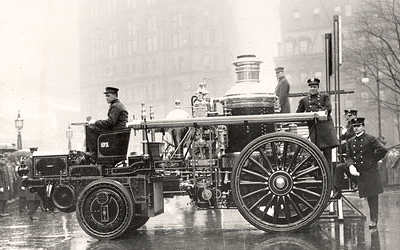 early photo of horse drawn steam fire engine converted to tractor driven.