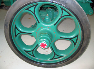 Cast iron wheel with solid rubber tire on 5R commercial truck restoration.