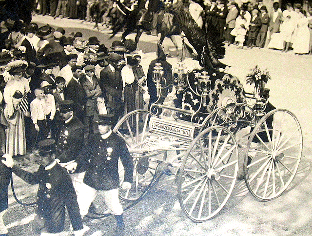 Parade photo of Ansonia hose carriage with stuffed eagle on top.